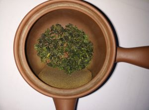 Kanne mit trockenen Teeblättern